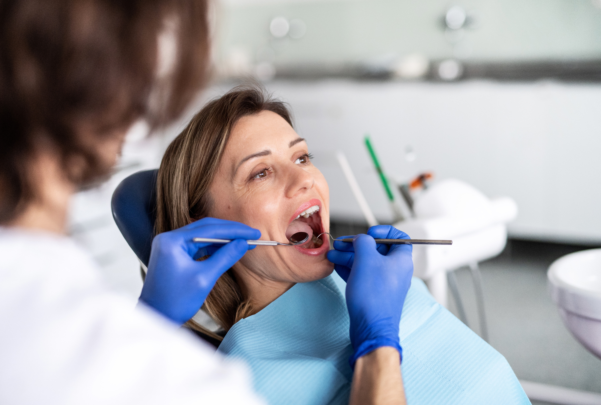 A woman has a dental check-up in dentist surgery.