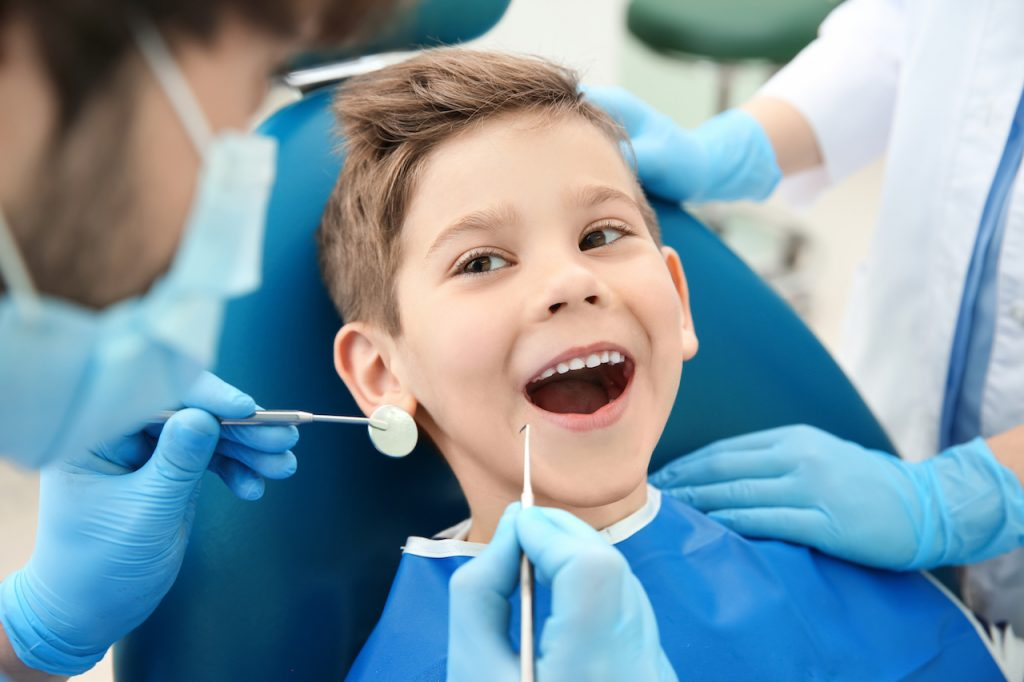 Dentist,Examining,Little,Boy's,Teeth,In,Clinic